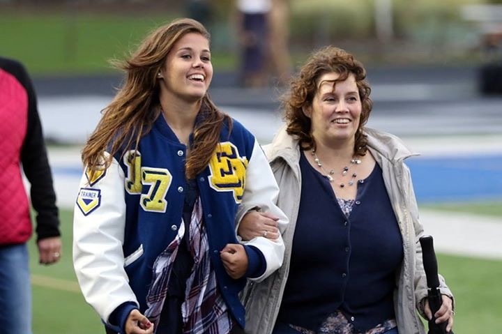 Abbie Peterson walks down the football field with her mother during senior night.