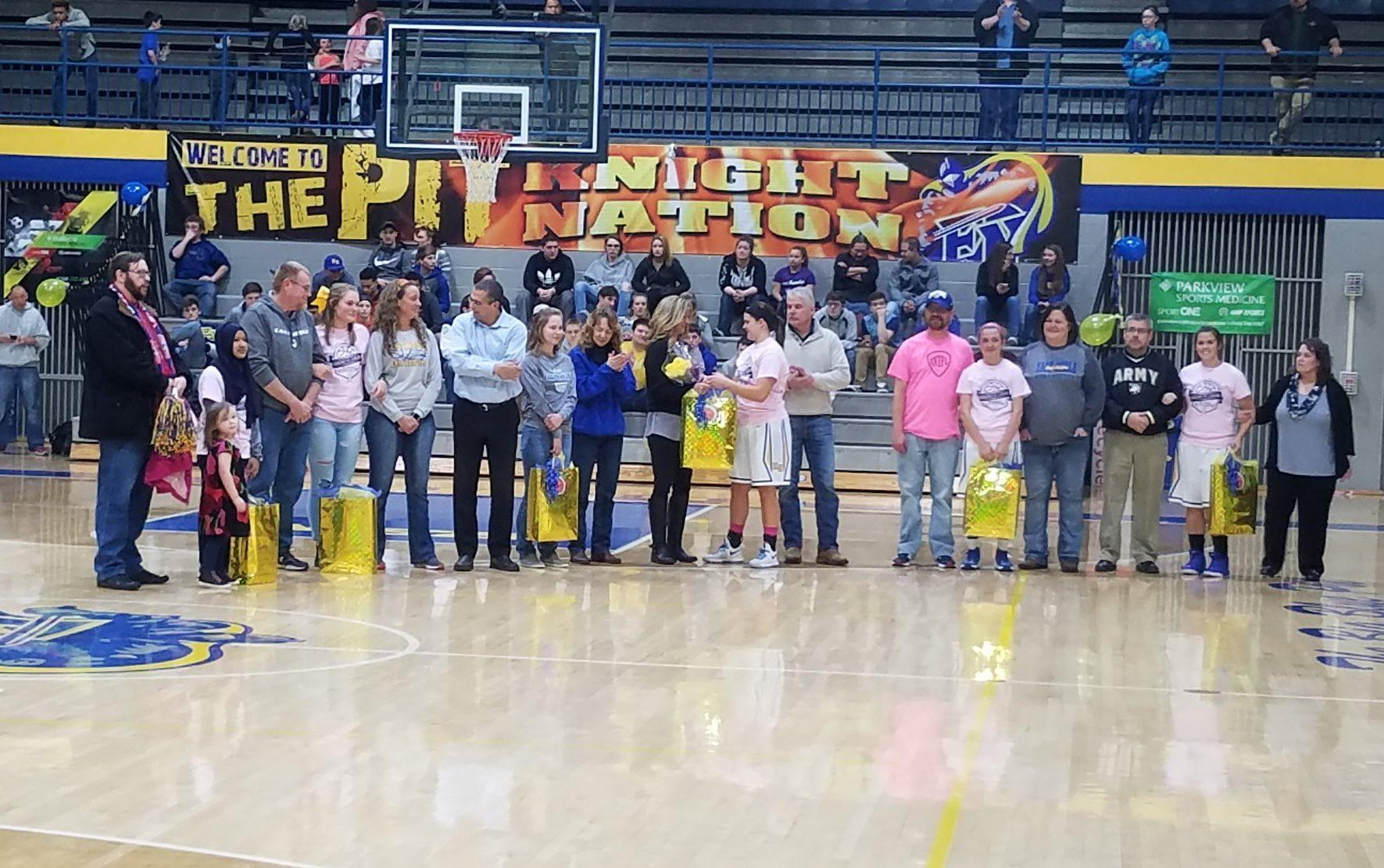 The seniors of the varsity girls basketball team standing with their parents. From left to right (students): Ceudah Hajashafira, Shelby Henschen, Jessica Vandiver, Lanie Allen, Kendaya Mapes, and Abbie Peterson