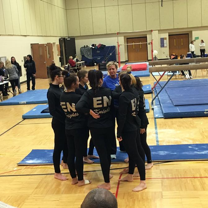 The+gymnastics+team+prepares+in+a+group+huddle+before+their+invitational+meet+on+the+7th.+