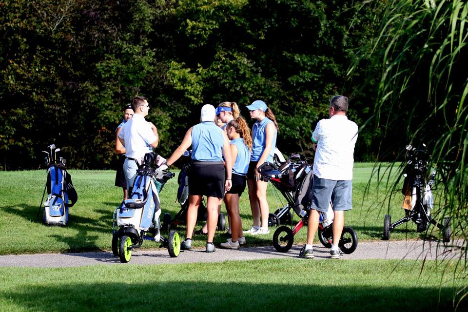 The Girls Golf team huddles around coach Mr. Ryan Eakins for a team meeting.